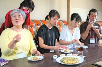 「ニューゴーヤーチャンプルー」を試食し、笑顔を浮かべる参加者ら=10月28日、北中城村中央公民館