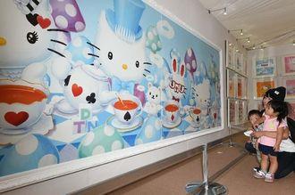 「キティちゃんかわいい」。大きな絵画作品に見入る親子連れ=21日午前、豊見城市・豊崎ライフスタイルセンターTOMITON