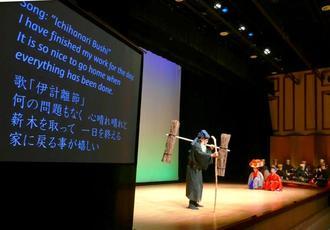 日本語と英語の字幕でせりふと歌意が表示された「花売の縁」=2月、那覇市・テンブスホール