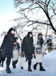 雪道を大学入試センター試験の会場に向かう受験生=13日午前、山形県米沢市