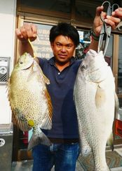 糸満釣りイカダで57センチ、2.09キロのコロダイと41.5センチ、1.23キロのカーエーを釣った山里高幸さん=13日