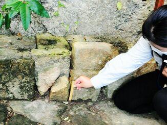 紛失後、取り替えられた石材部分を定規で示す南城市職員=5日、南城市知念