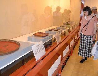 亀形の酒器や琉球漆器に見入る人たち=4日、那覇市・首里城公園