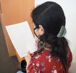 買ってきた履歴書を手にするネパール出身の女性=20日、那覇市内