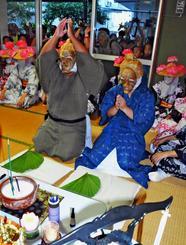 多くの見物客が見守る中、訪問先の仏壇に手を合わせるウシュマイ(左)とンミー=15日、石垣市登野城