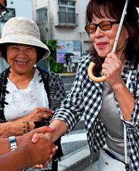 那覇市議選の立候補者と握手を交わす有権者=2日、那覇市内