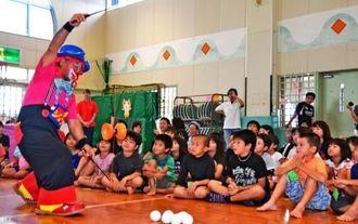 クラウン・ジョージさん(左)の芸に見とれる子どもたち=浦添市の経塚児童センター