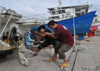 台風16号を警戒し、漁船をロープで固定する漁業者関係者ら=14日、石垣市・登野城漁港
