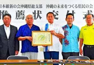 前宜野湾市長の佐喜真淳氏(中央)に推薦証書を交付した日本維新の会県総支部の儀間光男代表(左から2人目)=30日、那覇市のいとみね会館