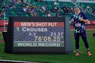世界新記録を示す掲示板の横に立つライアン・クラウザー=18日、米オレゴン州ユージン(AP=共同)