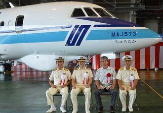 新型ジェット機「ちゅらたか」と名付け親の稲福馨さん(右から2人目)=12日、那覇航空基地