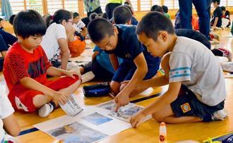 テーマに合わせた記事や写真を貼り付け、切り抜き新聞を作る児童=名護市立久辺小学校