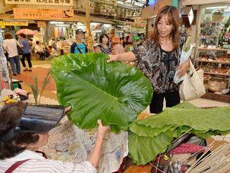 仏壇の供え物などを買い求める人たちでにぎわう市場=7日午後、那覇市牧志の市場本通り