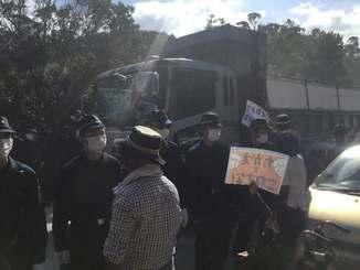 ヘリパッド建設で、ゲート内に入る大型ダンプカーに抗議する市民ら=11日午前10時、東村高江