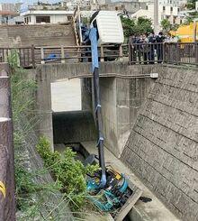 ユニック車が傾き、男性が挟まれた現場=28日、那覇市松島