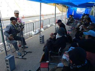 スピーチの合間には歌も歌いながら、基地建設に抗議の意を示す市民ら=28日午前11時すぎ、名護市・辺野古