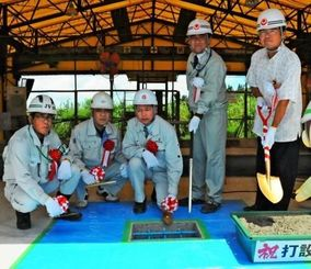 セグメントの製作を終えたことを祝い、「打設式」を行った工事関係者=6月30日、宮古島市の製作ヤード