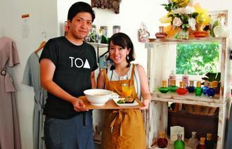 店を営む玉城武蔵さん(左)と美希さん夫妻。アロマランプとオイルのセットはキャンペーンで6千円から販売している=浦添市港川