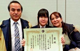 審査員特別賞を受賞した上地リオンさん(中央)と母親の靖枝さん(右)、砂川恵長教頭=22日、東京都千代田区