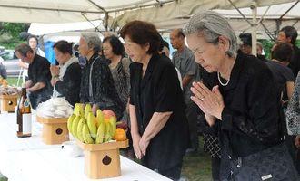 10・10空襲の慰霊祭で焼香する参列者=10日午後、那覇市若狭の若狭海浜公園「なぐやけの碑」