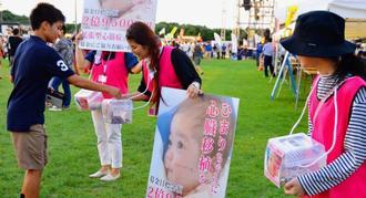 祭り会場で陽茉莉ちゃんの募金を呼び掛ける救う会のメンバー=14日、宜野湾海浜公園多目的広場