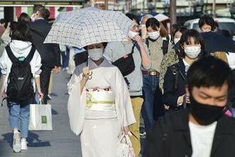 21日午後、京都市内をマスク姿で歩く人たち