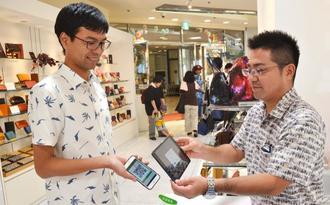 中国人向けのモバイル決済サービス「WeChat Pay」を使う店員と客=30日、那覇市のデパートリウボウ