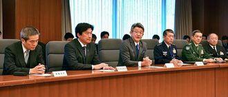 沖縄基地負担軽減推進委員会の初会合であいさつする委員長の武田良太副大臣(左から3人目)=22日、防衛省