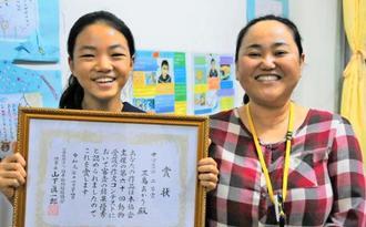 動物愛護の作文コンテストで入賞した三島あかりさん(左)と與那國充子教諭=28日、石垣市・白保中学校