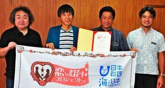 波房克典会長(左から2人目)から「恋する灯台のまち」として認定証を受け笑顔を見せる中山義隆市長(同3人目)=石垣市役所