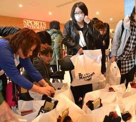 新春初売りでお目当ての人気ブランドの福袋を手にする人たち=1日午前9時ごろ、北中城村・イオンモール沖縄ライカム