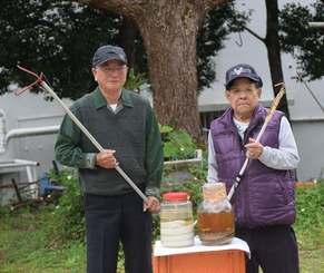 製作したハブ捕獲器を持つ棚原浩さん(右)と友人の宜野座晃さん=6日、宜野湾市志真志・棚原さん宅