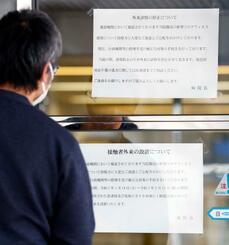 済生会有田病院に張り出された、接触者外来設置を知らせる文書(下)などを見る人=14日午後、和歌山県湯浅町