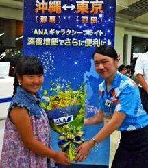18日に那覇を飛び立ったANAのギャラクシーフライトで花束を受け取る乗客(全日本空輸提供)