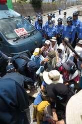 キャンプ・シュワブのゲート前に座り込む市民らを強制排除する県警機動隊員ら=5日正午すぎ、名護市辺野古