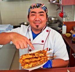 「おいしいよ!」とできたての沖縄風アンティクーチョを手にする山城さん=サンタクルス市内