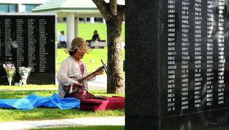 <平和の礎>戦没者の名前が刻まれた石碑の前で三線を弾く女性=23日午前、糸満市