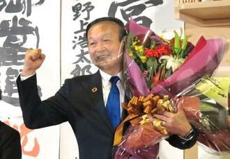 富山市長選で初当選し、花束を手にポーズをとる藤井裕久氏=18日夜、富山市