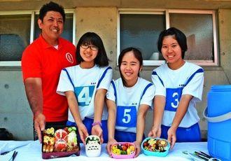 伊志嶺澄人先生(左端)と力作を出品した生徒たち=西原町陸上競技場