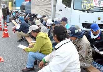 工事車両の進入を警戒し、米軍キャンプ・シュワブゲート前に座り込む人たち=8日午前7時32分、名護市辺野古