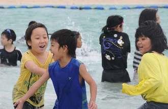 肌寒い風が吹き付ける中、ビーチで元気に遊ぶ子どもたち=22日、南城市・あざまサンサンビーチ