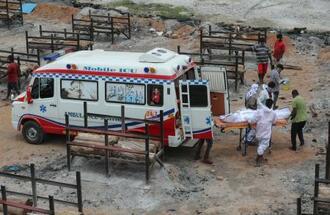 新型コロナウイルスに感染し亡くなった人の遺体が運び込まれている開放型火葬場=12日、インド・カルナタカ州ベンガルール(AP=共同)