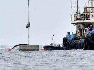 クレーンで海中に下ろされる大型コンクリートブロック=7日午前10時、名護市辺野古沖