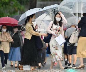 降りしきる雨の中、傘を差して歩く人たち=22日午後5時26分、那覇市久茂地(国吉聡志撮影)