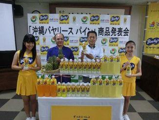 県産果汁を使った「沖縄バヤリース パイン」の発売をPRする納所社長(右から2人目)、砂川理事長(同3人目)=那覇市、JAおきなわ本店