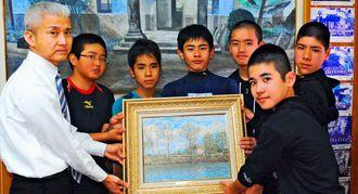 泊小の上田正弘校長(左端)に絵画を手渡す泊メッツの卒団生=21日、那覇市立泊小学校