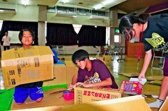 避難所で過ごすことを考え必要だと思うものを段ボールで作る児童ら=4日、宜野湾市社会福祉センター