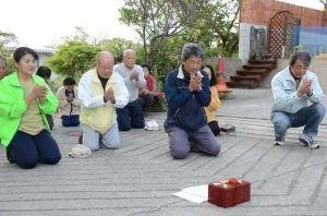 無病息災を願い、集落の入り口で祈る住民たち=沖縄市与儀