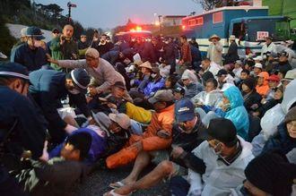 機動隊のごぼう抜きに抵抗し、新基地建設反対を訴えて座り込む市民ら=米軍キャンプ・シュワブのゲート前、14日午前6時半過ぎ