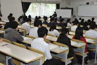 問題と解答用紙が配られ、試験開始を待つ受験生=25日午前、西原町・琉球大学